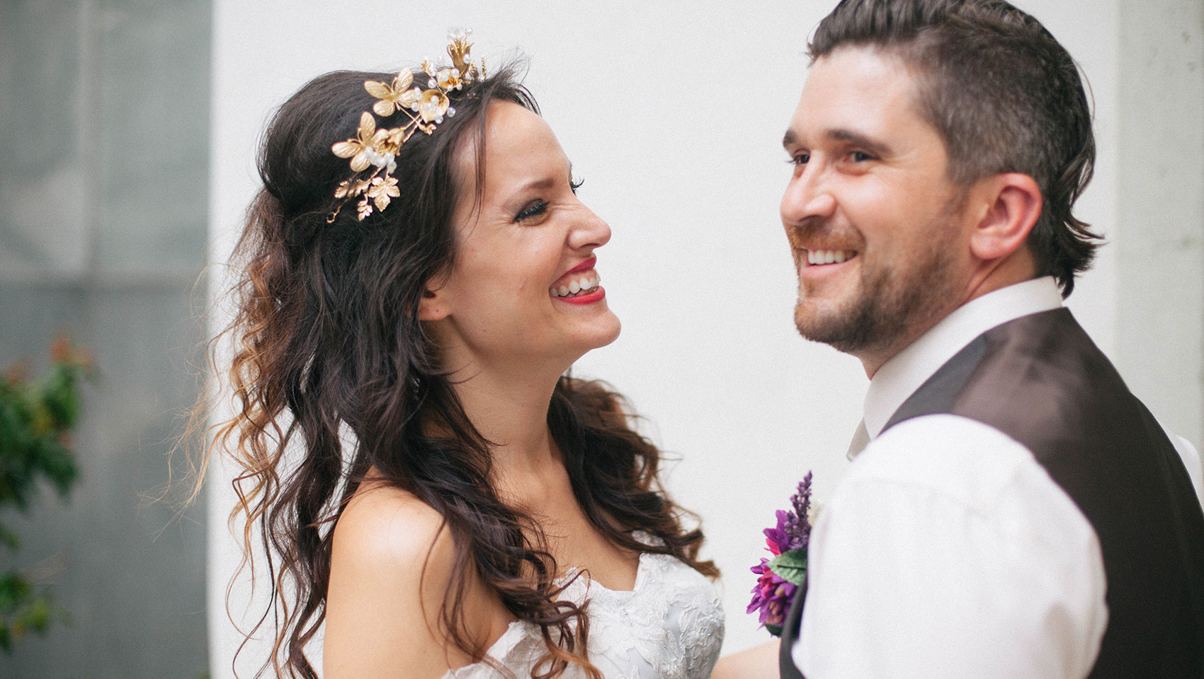bride with flower crown smiling with groom in tuxedo vest